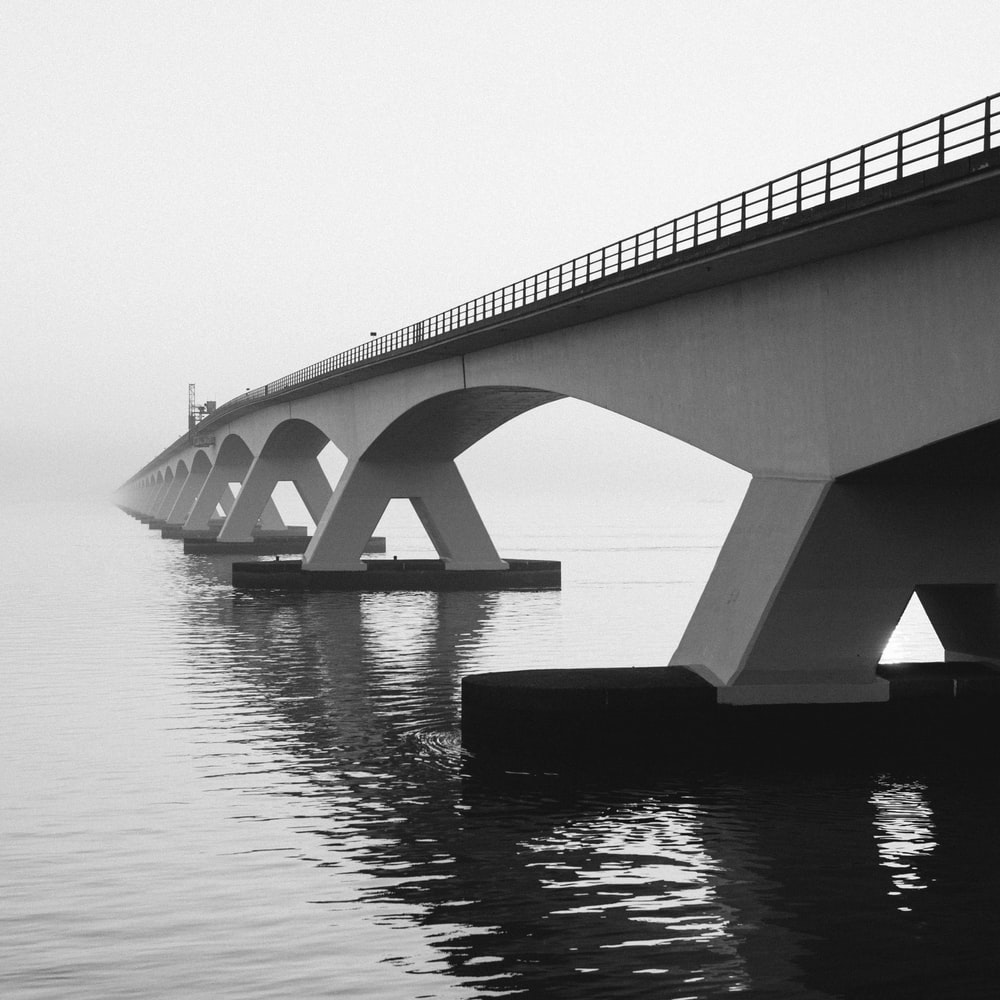 grayscale photography of bridge above water