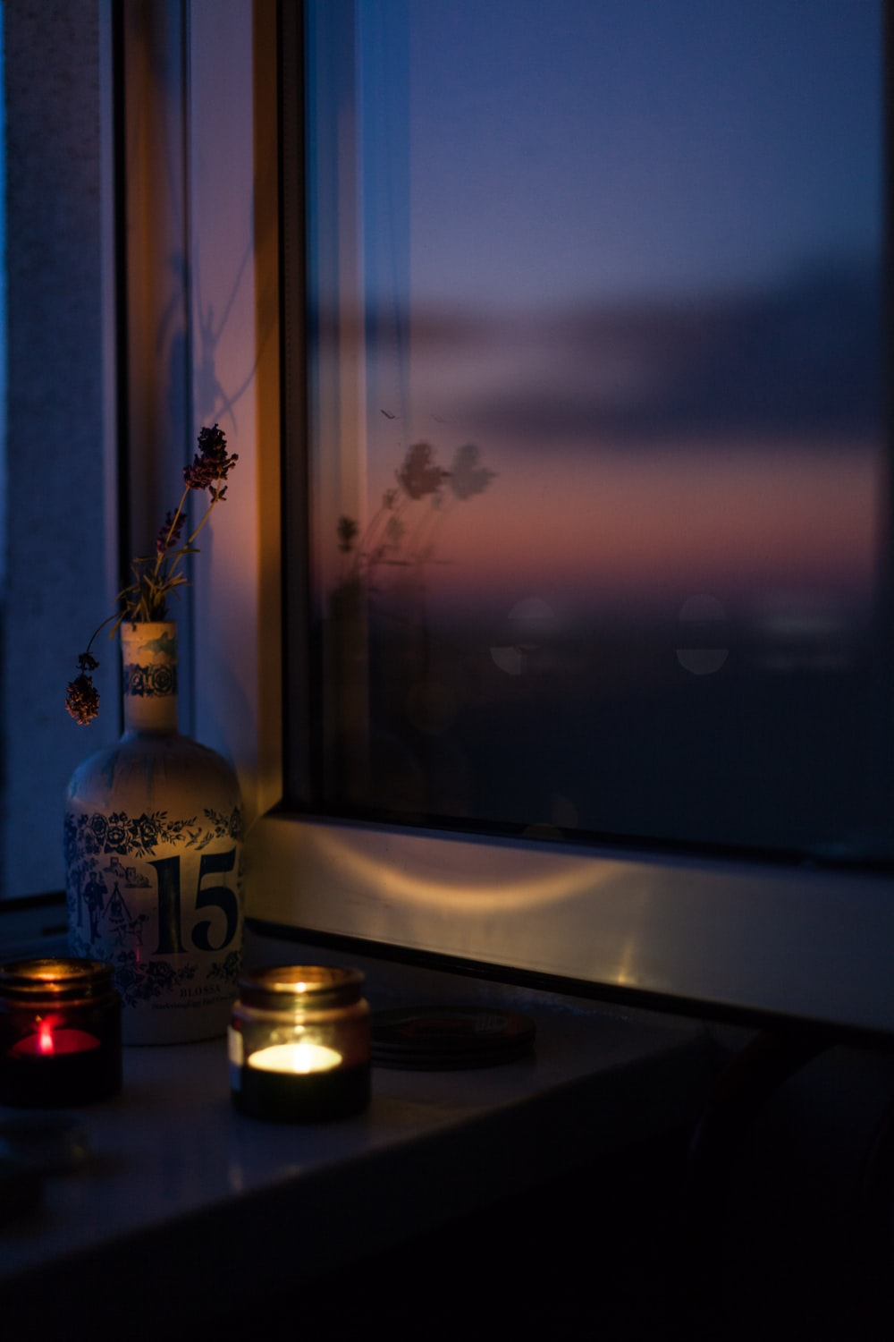 two lighted tealights near closed window