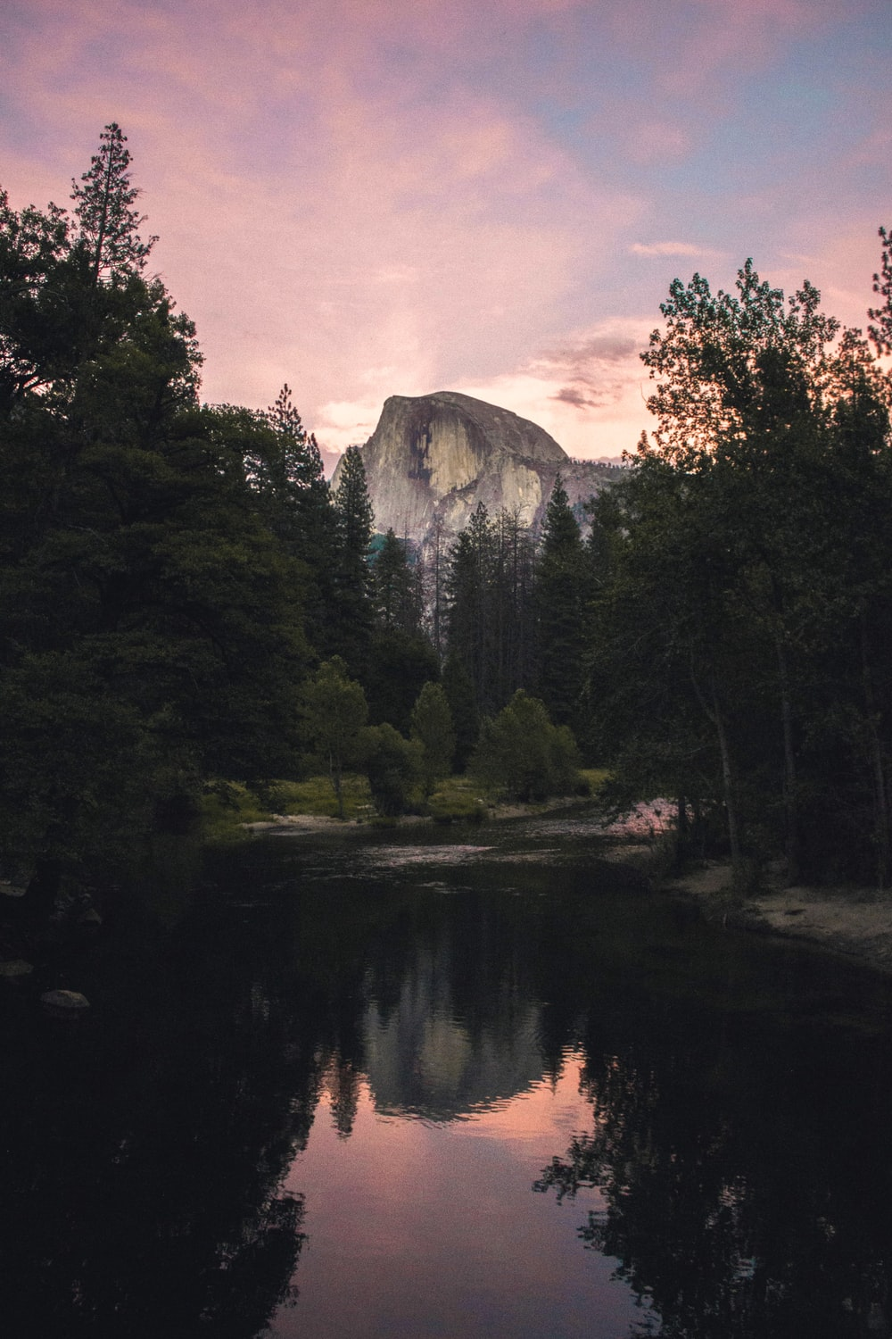 calm body of water near trees and mountain