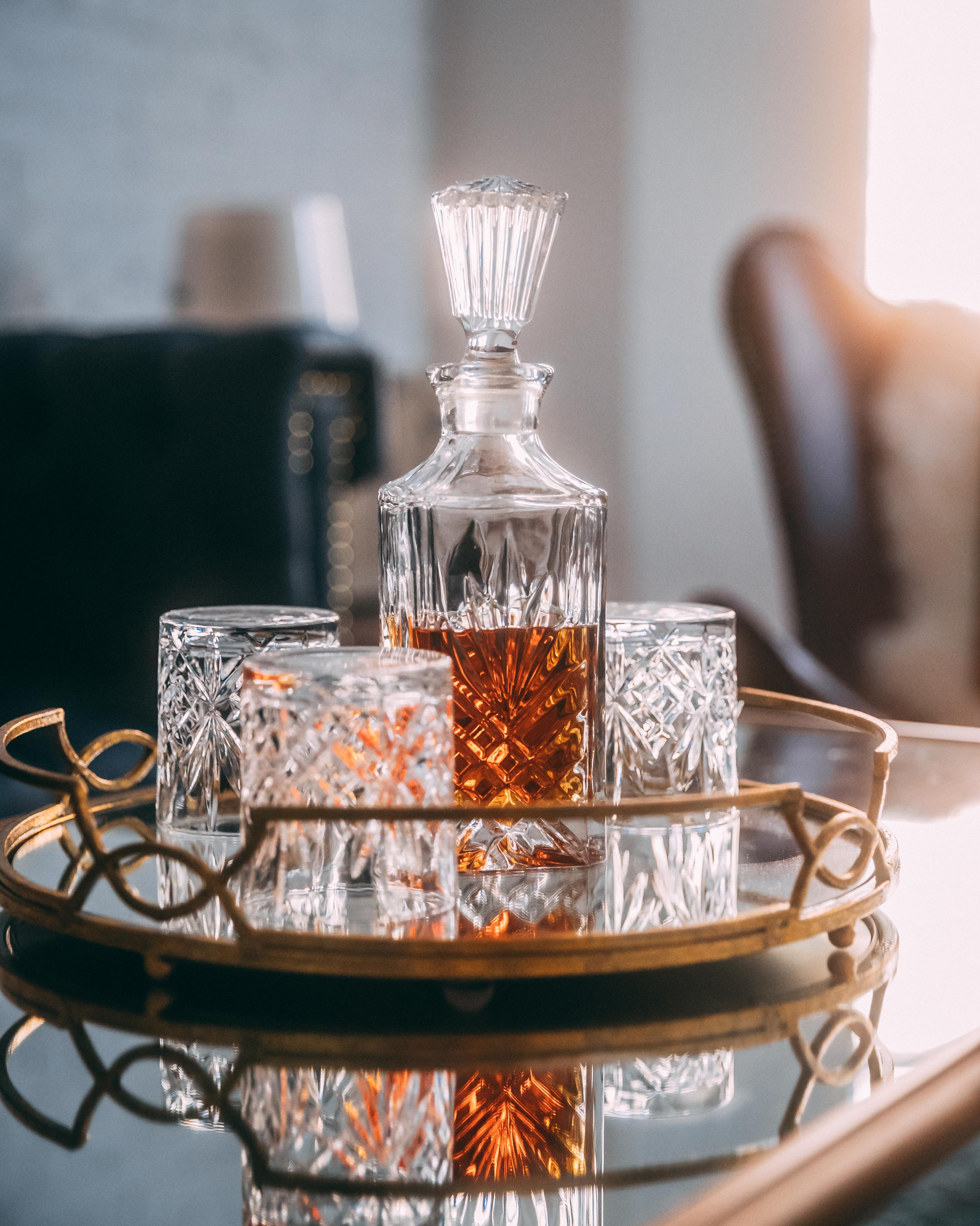 selective focus photography of liquor in decanter on mirror tray
