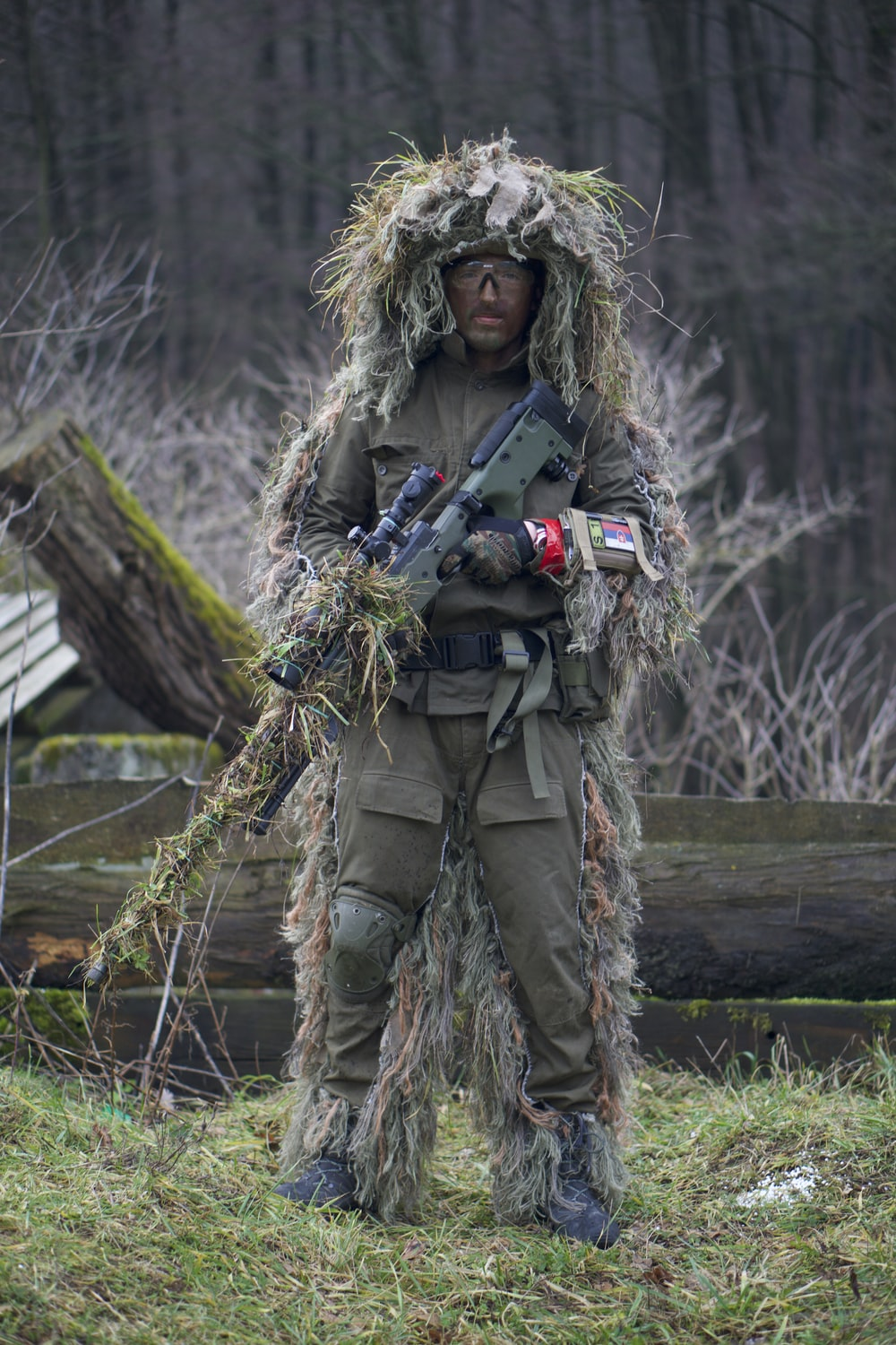 soldier covered with grass holding sniper rifle