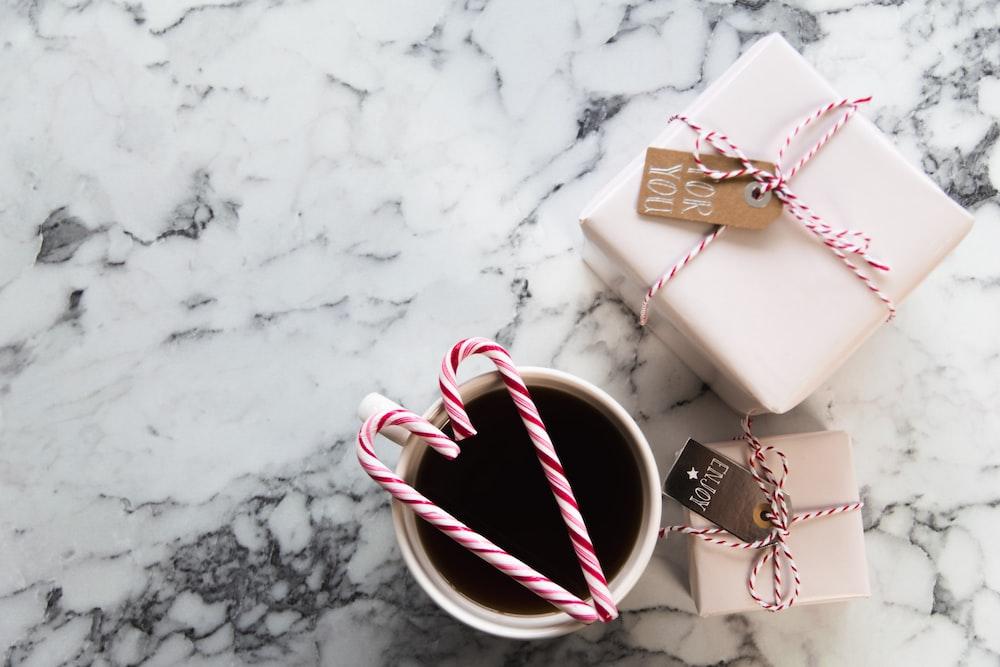 white ceramic mug beside gift boxes