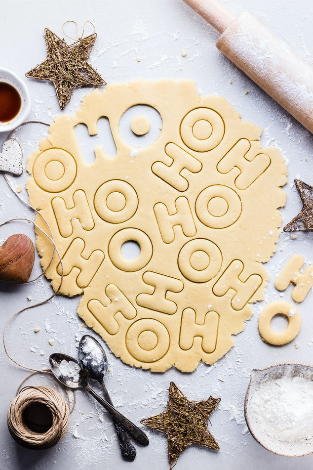 "Cookie dough rolled out on a white countertop, with cutouts that have ""H"" and ""O"" in it."