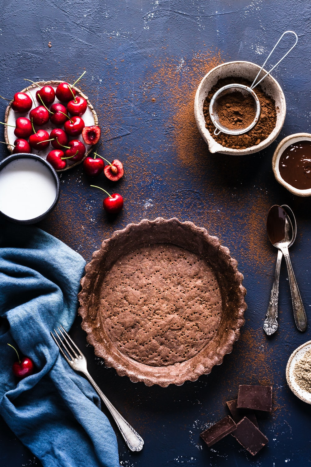 flat lay photograph of pie tray, cherries, and powder