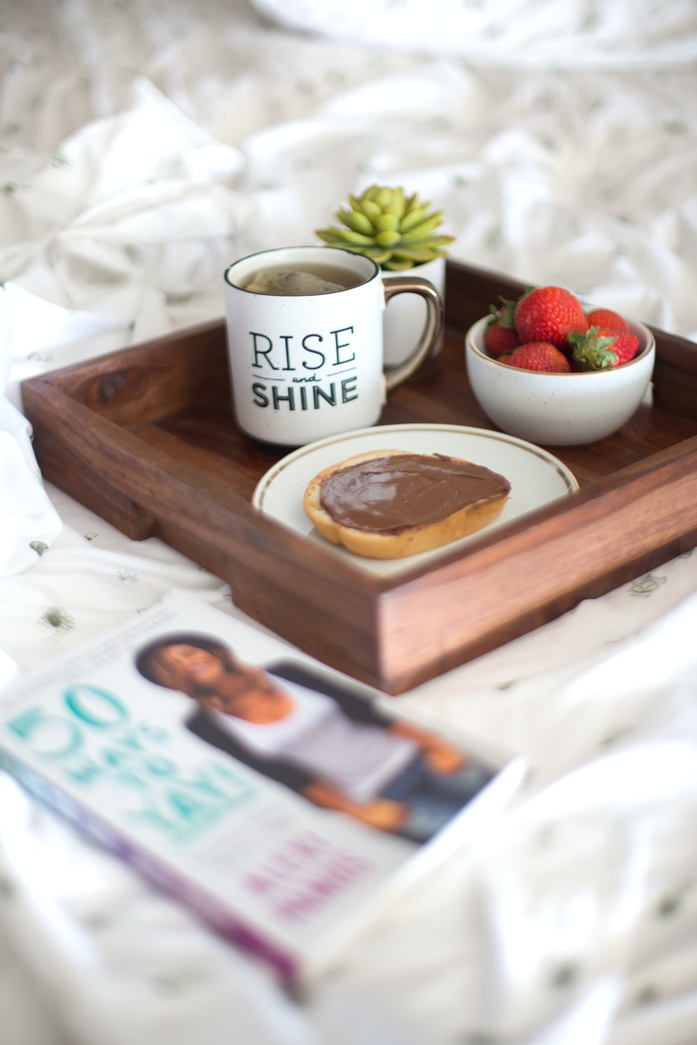 white Rise Shine ceramic mug on brown table