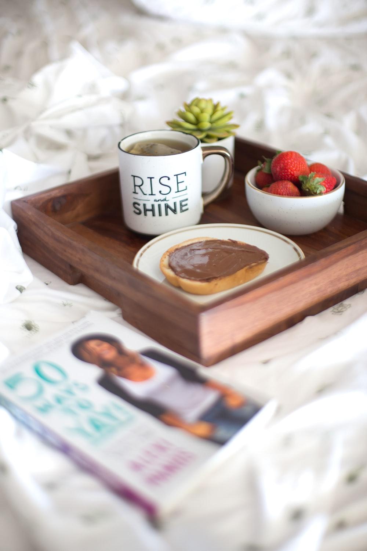 white Rise Shine ceramic mug on brown table