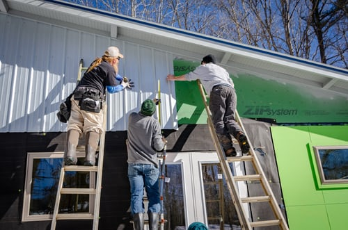 contractors putting siding on a house.