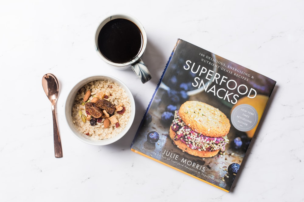 flat lay photography of coffee, Superfood Snacks magazine, and bowl of cereals