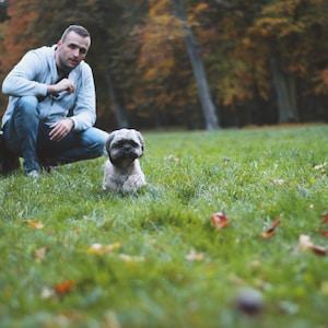 man on grass field near puppy during daytime
