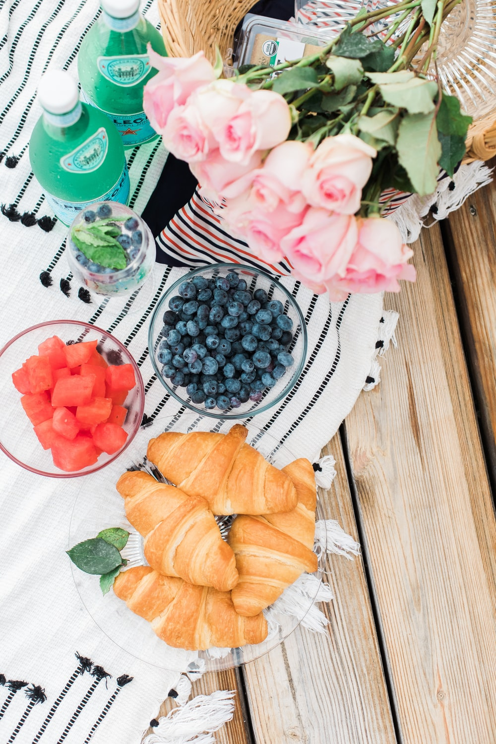 two bowl of fruits near plated breads