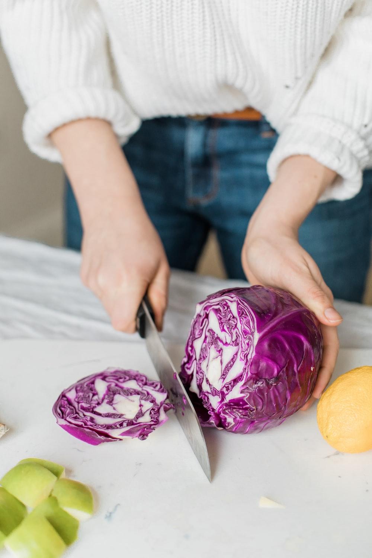 woman slicing purple vegetable