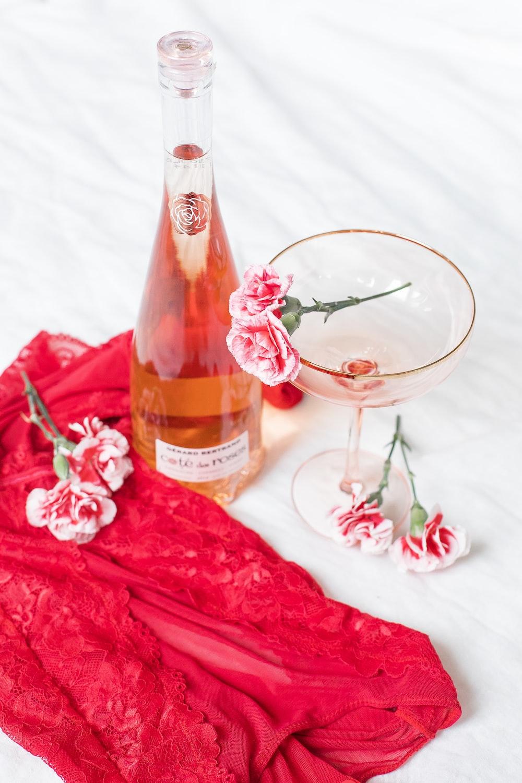 wine bottle near flowers on white textile