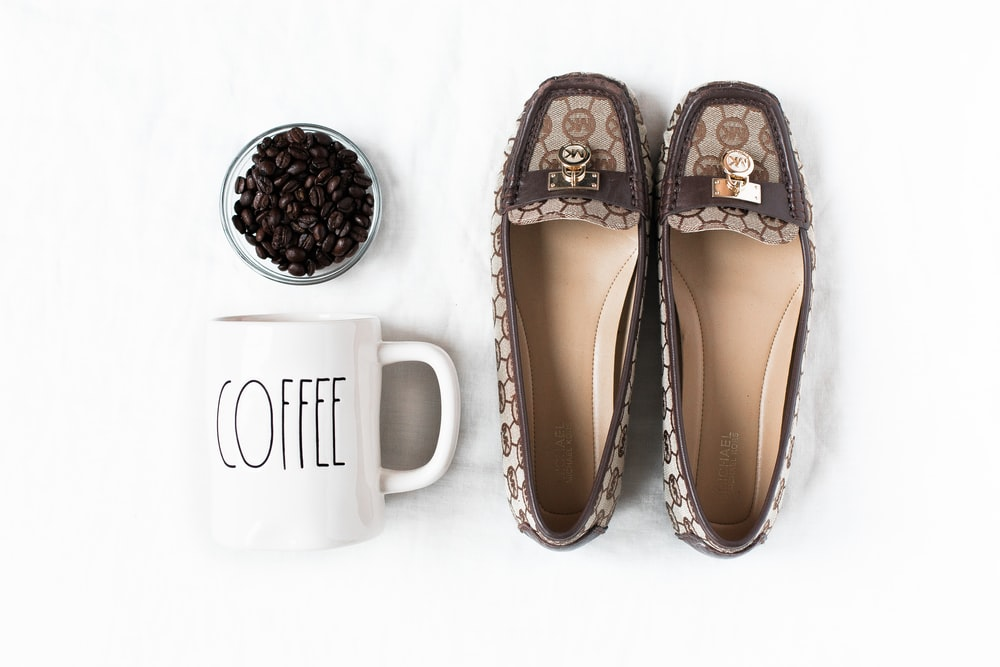 pair of brown flat shoes near mug