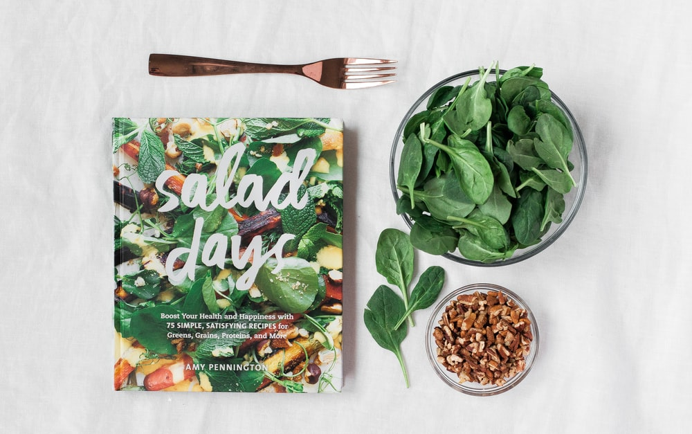 Salad day cookbook beside clear glass bowl with vegetable