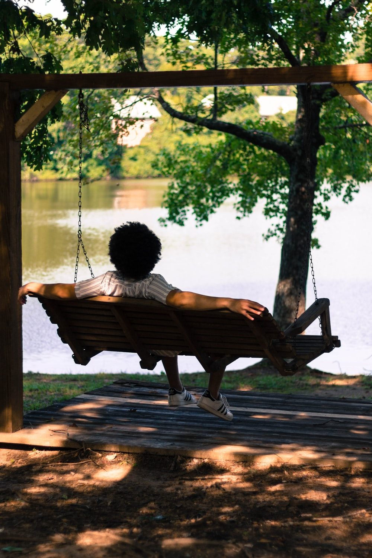 person sitting on hammock facing lake