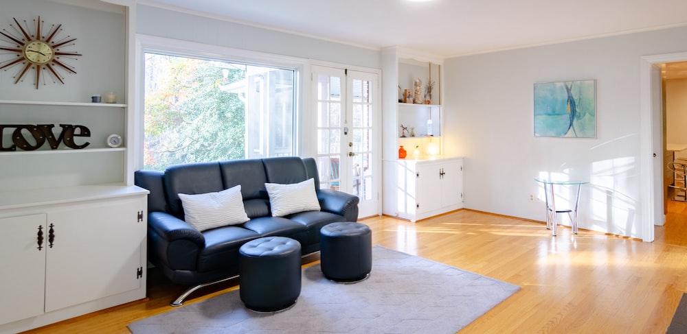 black leather sofa beside sideboard inside house