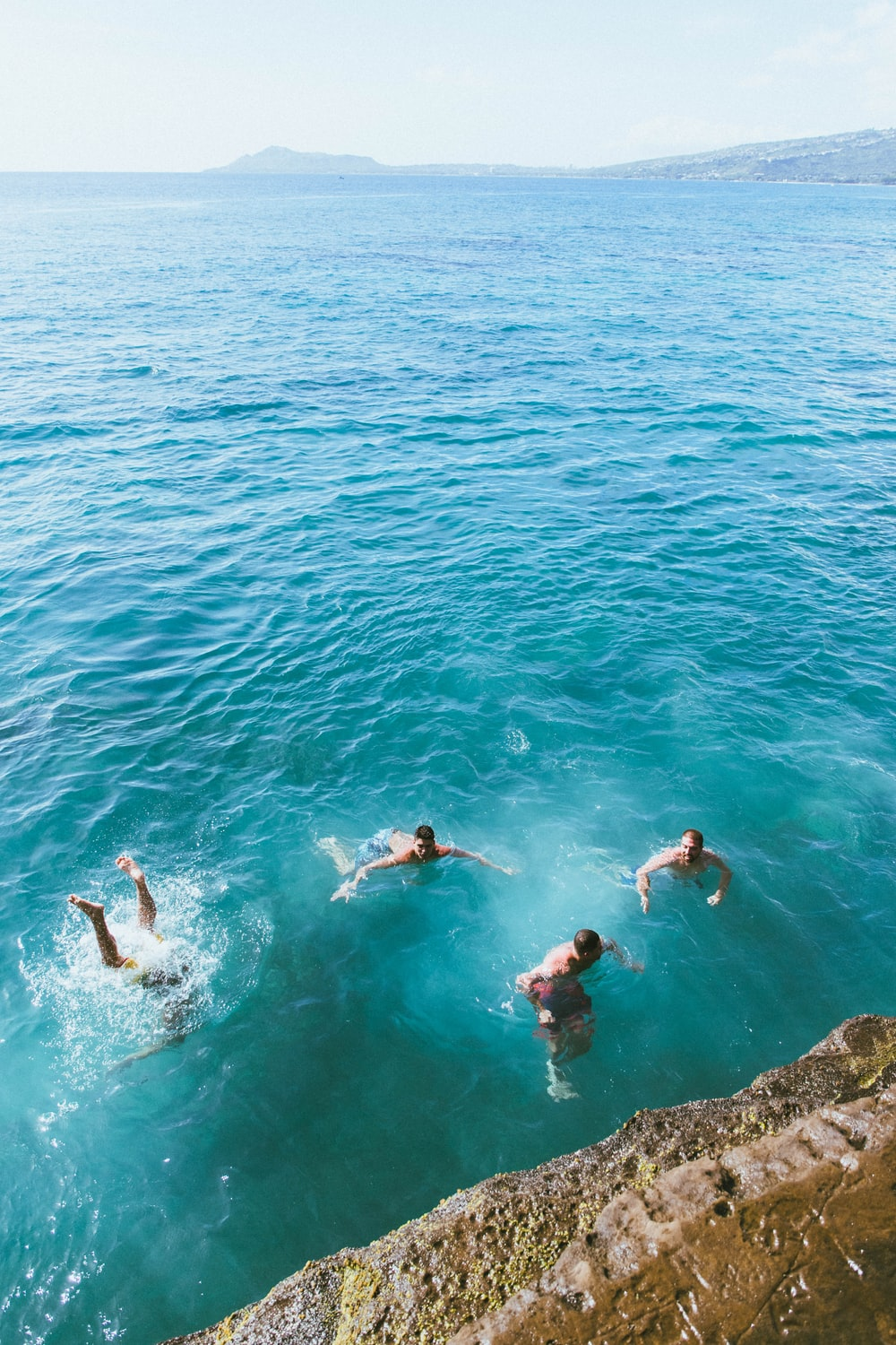 aerial photography of four men swimming in blue sea