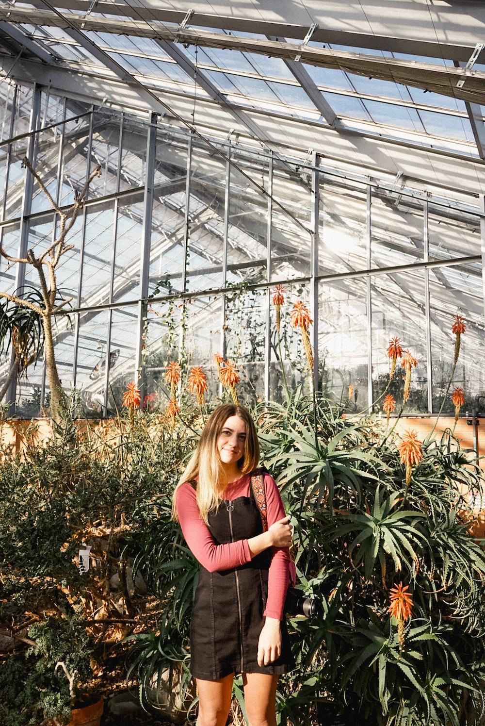 smiling woman standing near flower garden