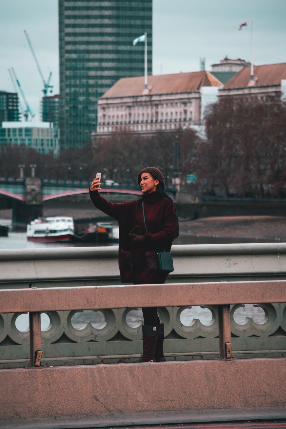 woman standing on bridge taking selfie