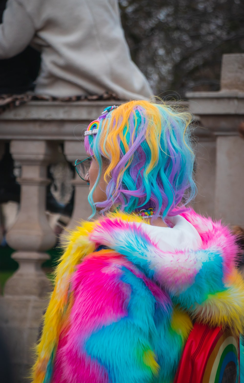 selective color photography of woman wearing blue, yellow, and pink coat and hair