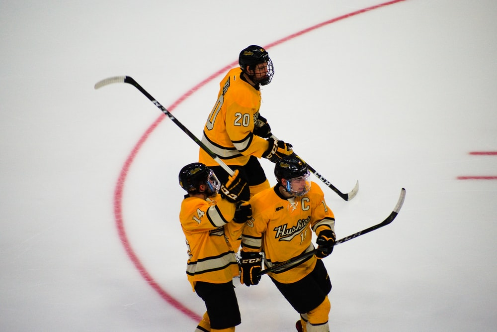 three hockey players on focus photography