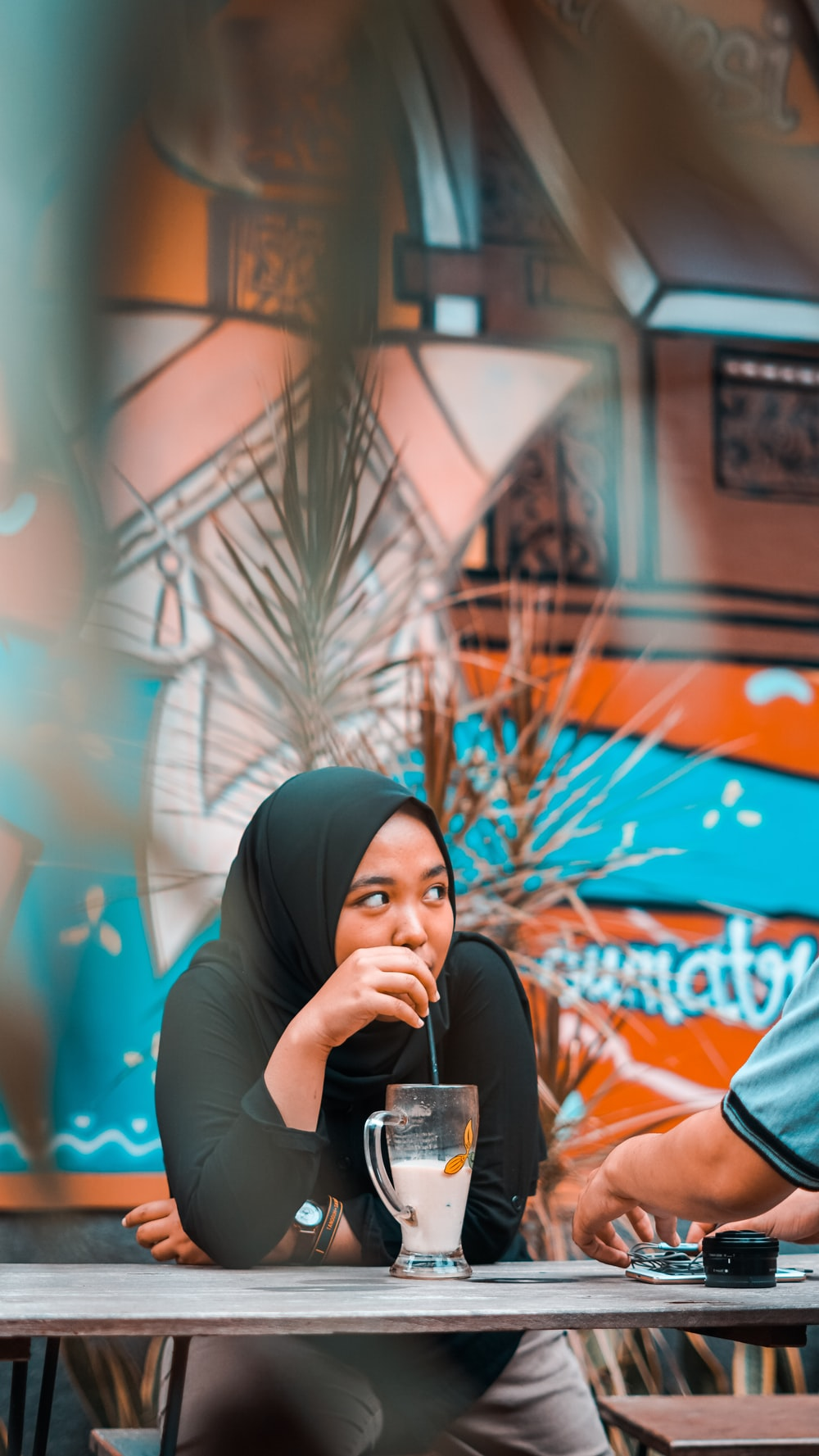 selective focus photography of woman in black hijab while drinking beverage