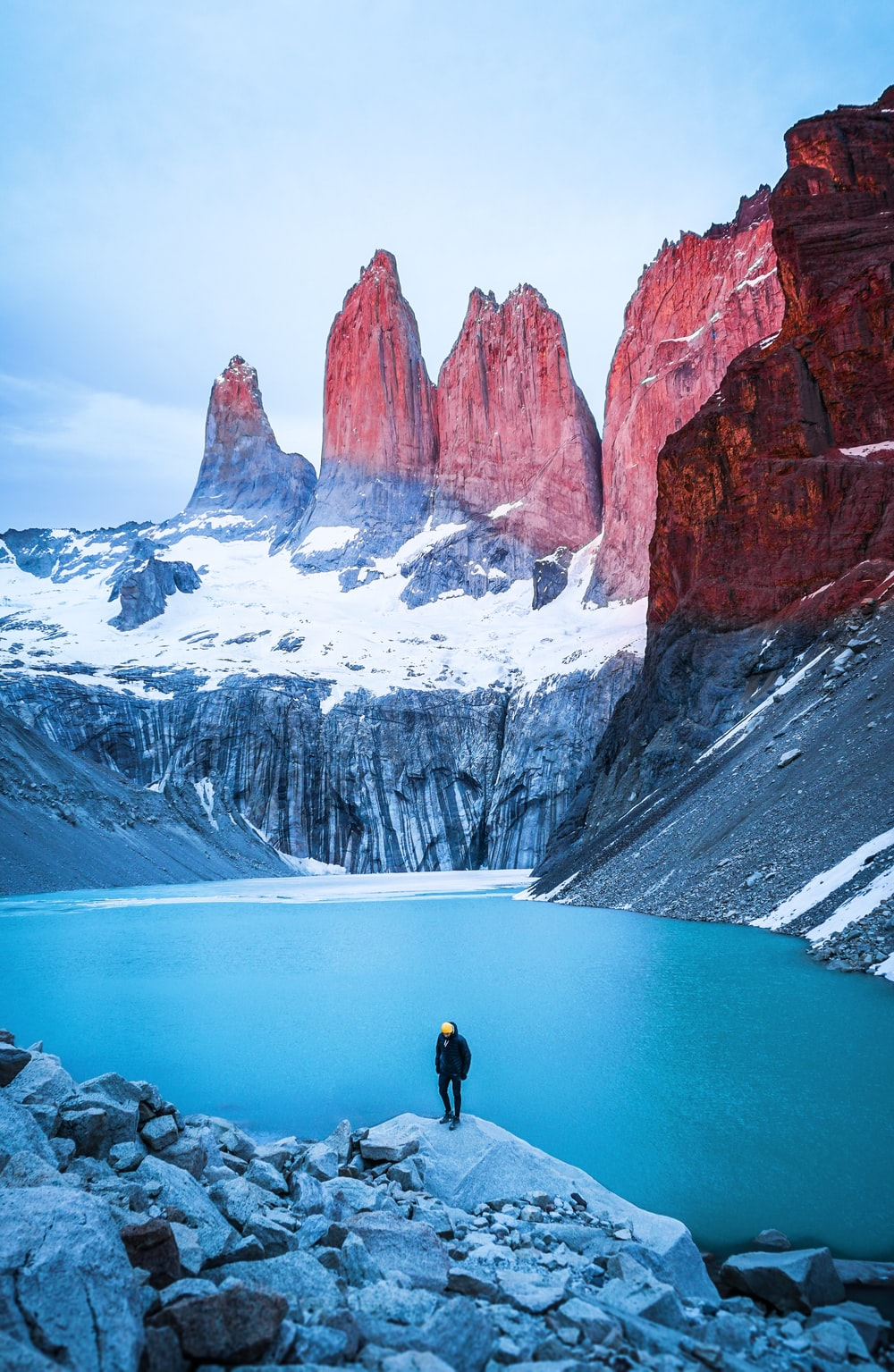 man standing on rock facing body of water and mountain