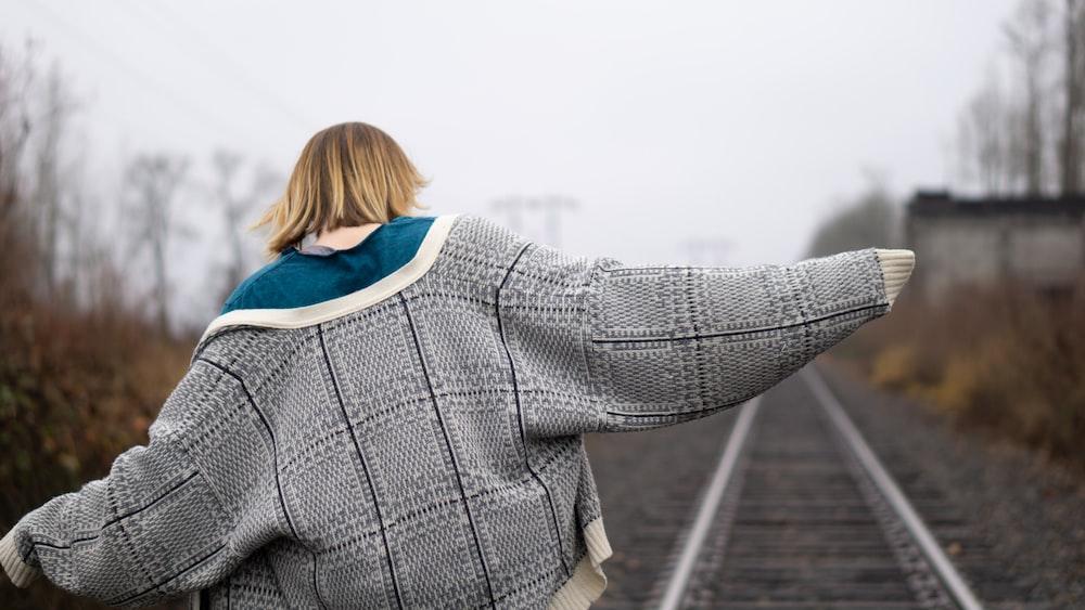 woman in gray coat walking on railway