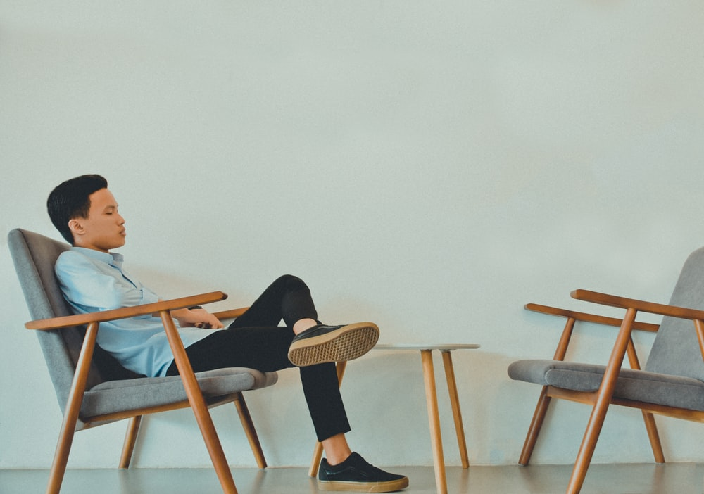 man sitting on gray fabric armchairs