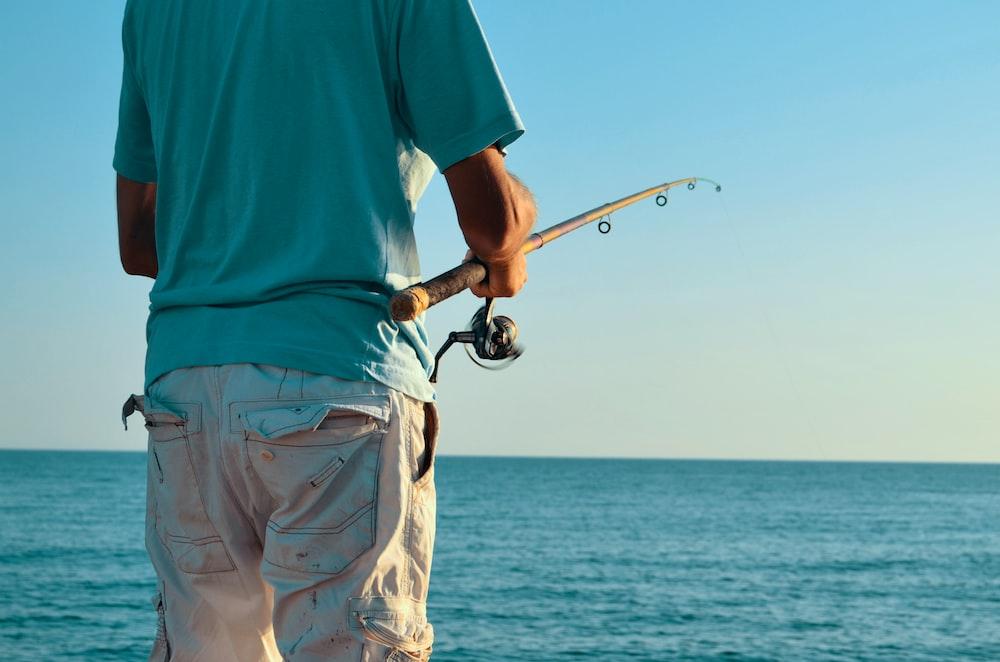 man holding fishing rod facing blue sea
