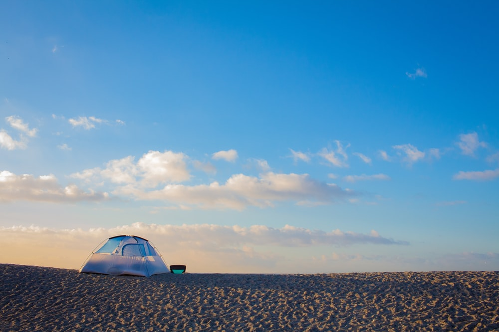 tent on sand under blue sky and white clouds