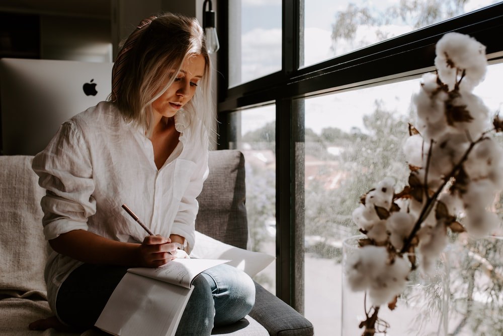 woman in white shirt sits and write in room