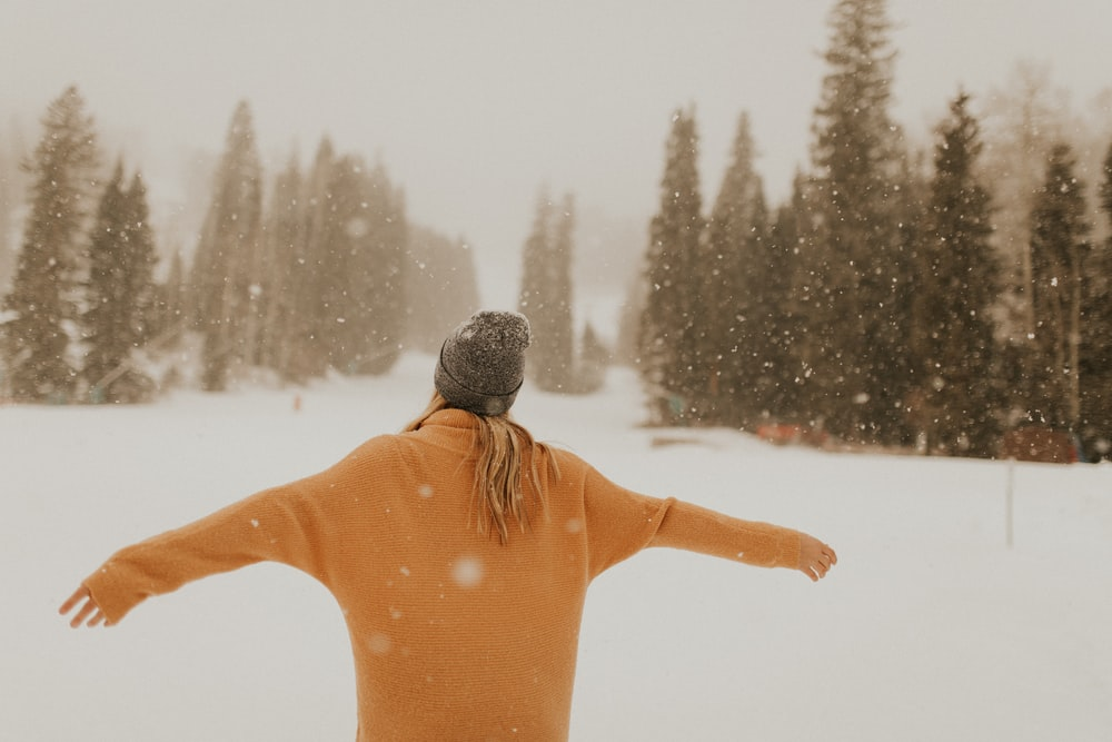 person wearing hoodie while standing on field of snow with arms wide open