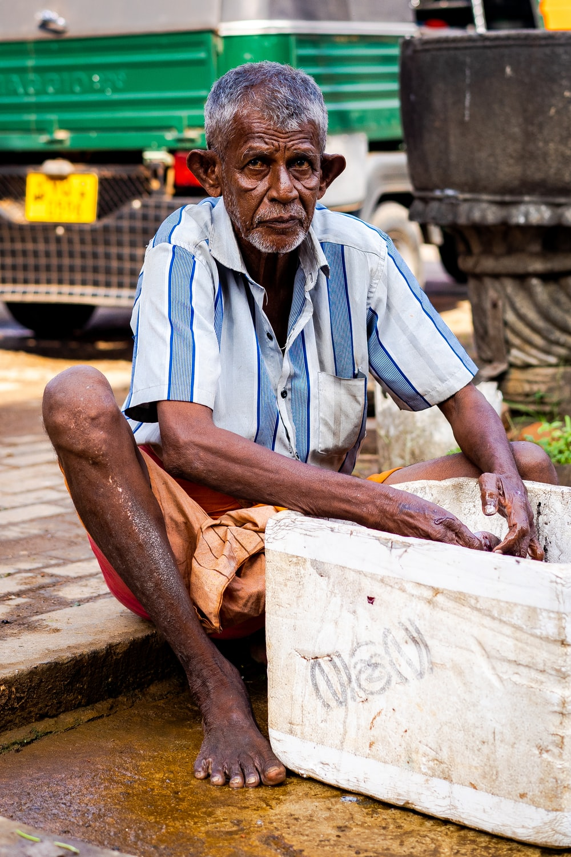 man wearing striped top holding styro ice box