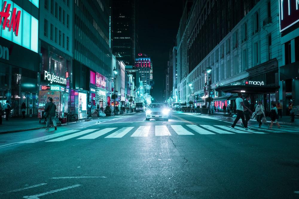 people walking on pedestrian near car