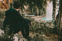 man sitting facing trees
