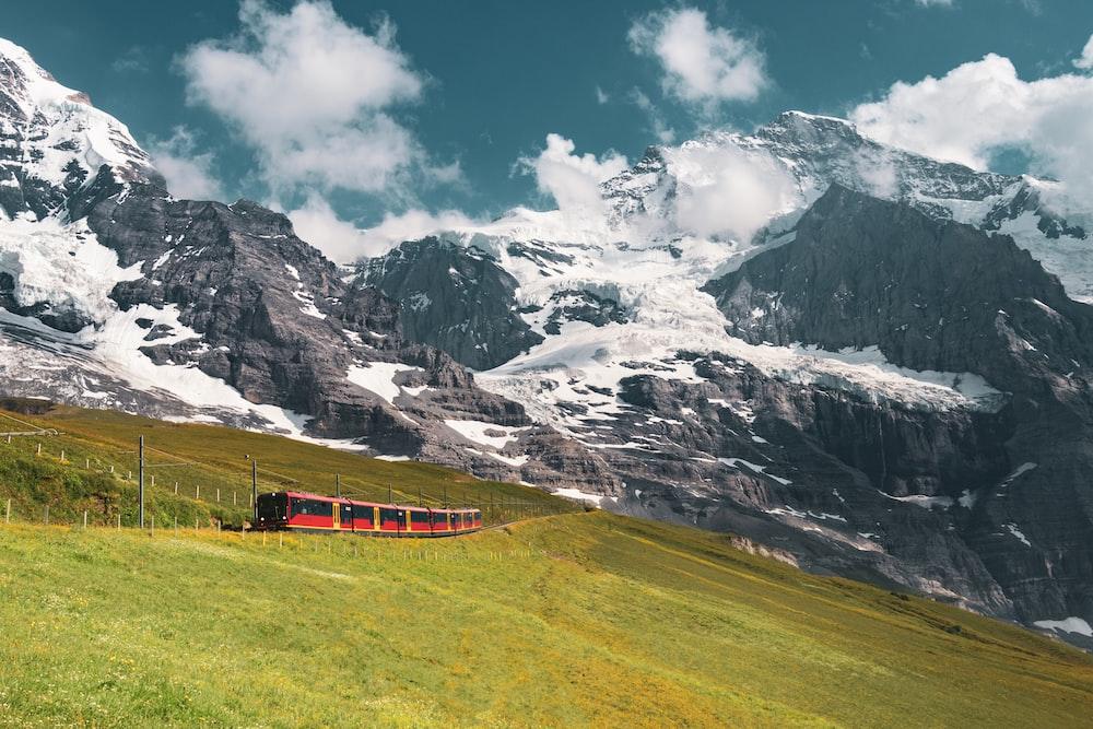 red train near mountain alps