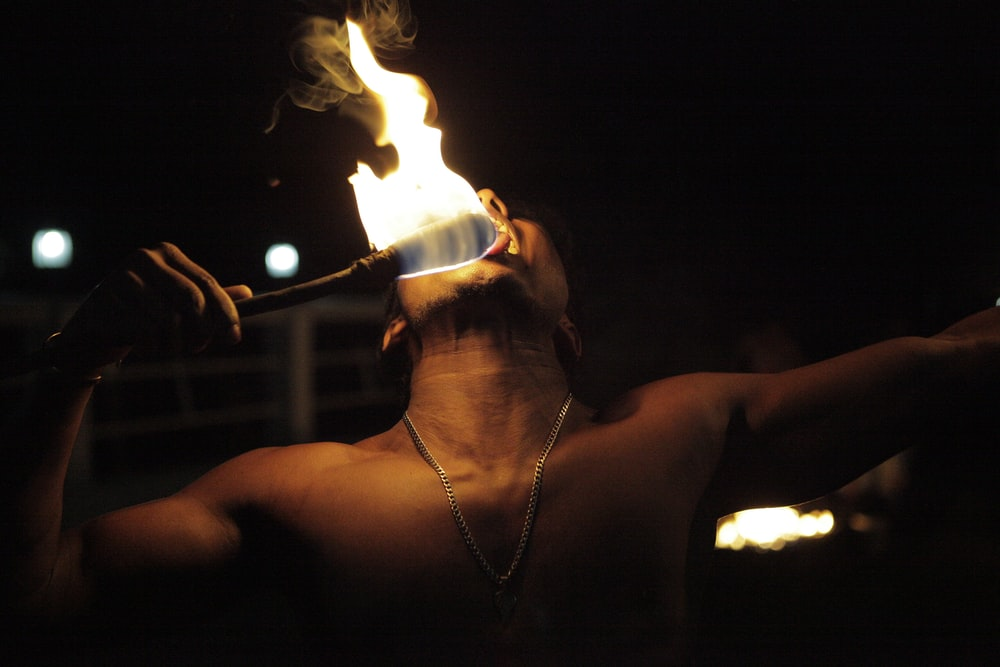 man playing fire in dim light