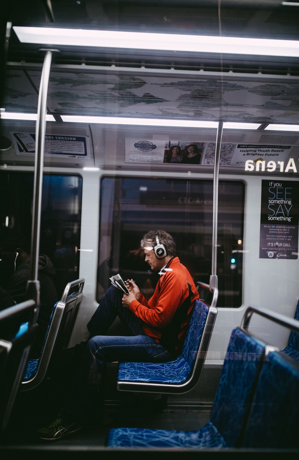 man sitting inside train while reading