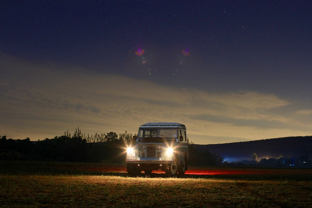 landscape photography of vehicle with turned-on headlights