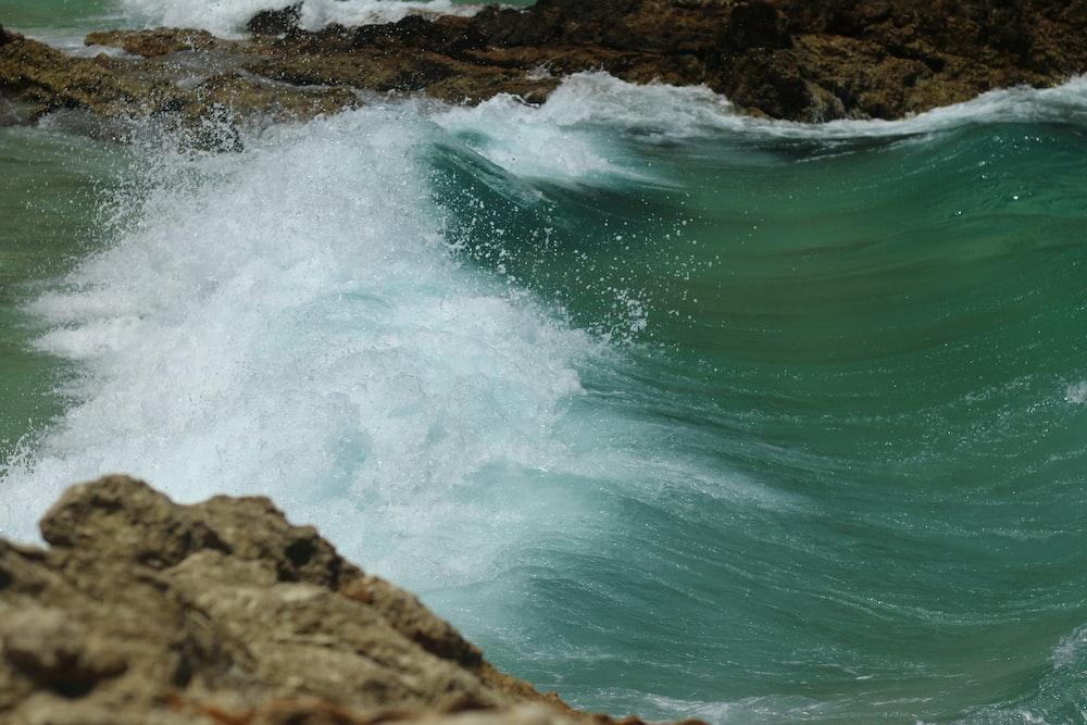 time-lapse photography of ocean waves splashing on rocks
