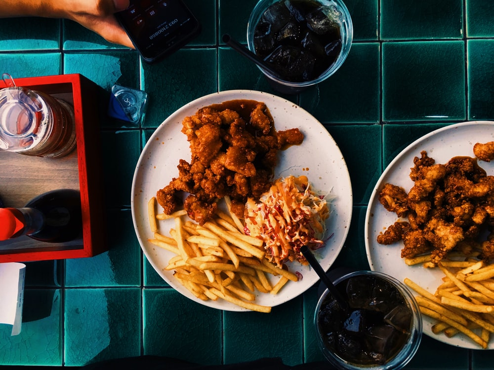 fried chicken and fried fries on white ceramic plate