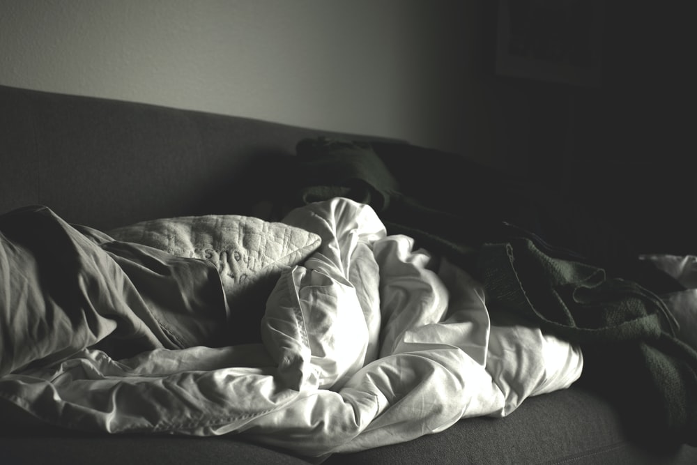 grayscale photography of crumpled blankets on sofa