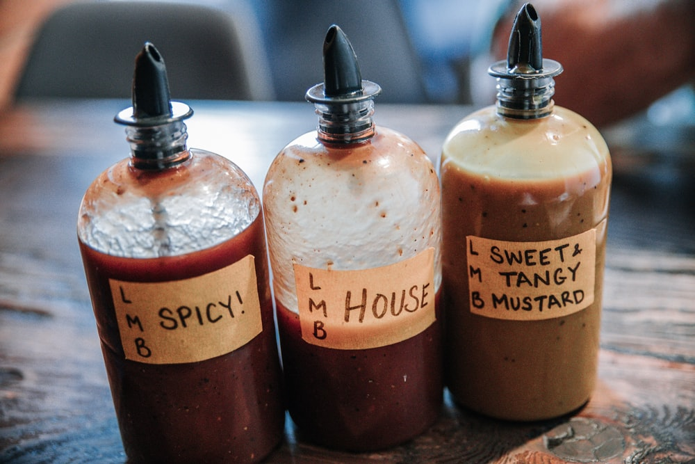 three filled condiment shakers on brown wooden surface