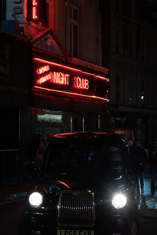 black card beside night club at night