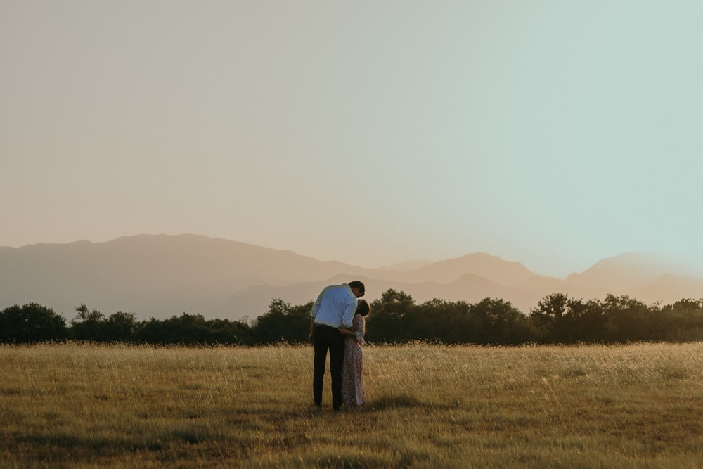 man and woman kissing in middle of plaid field during daytime
