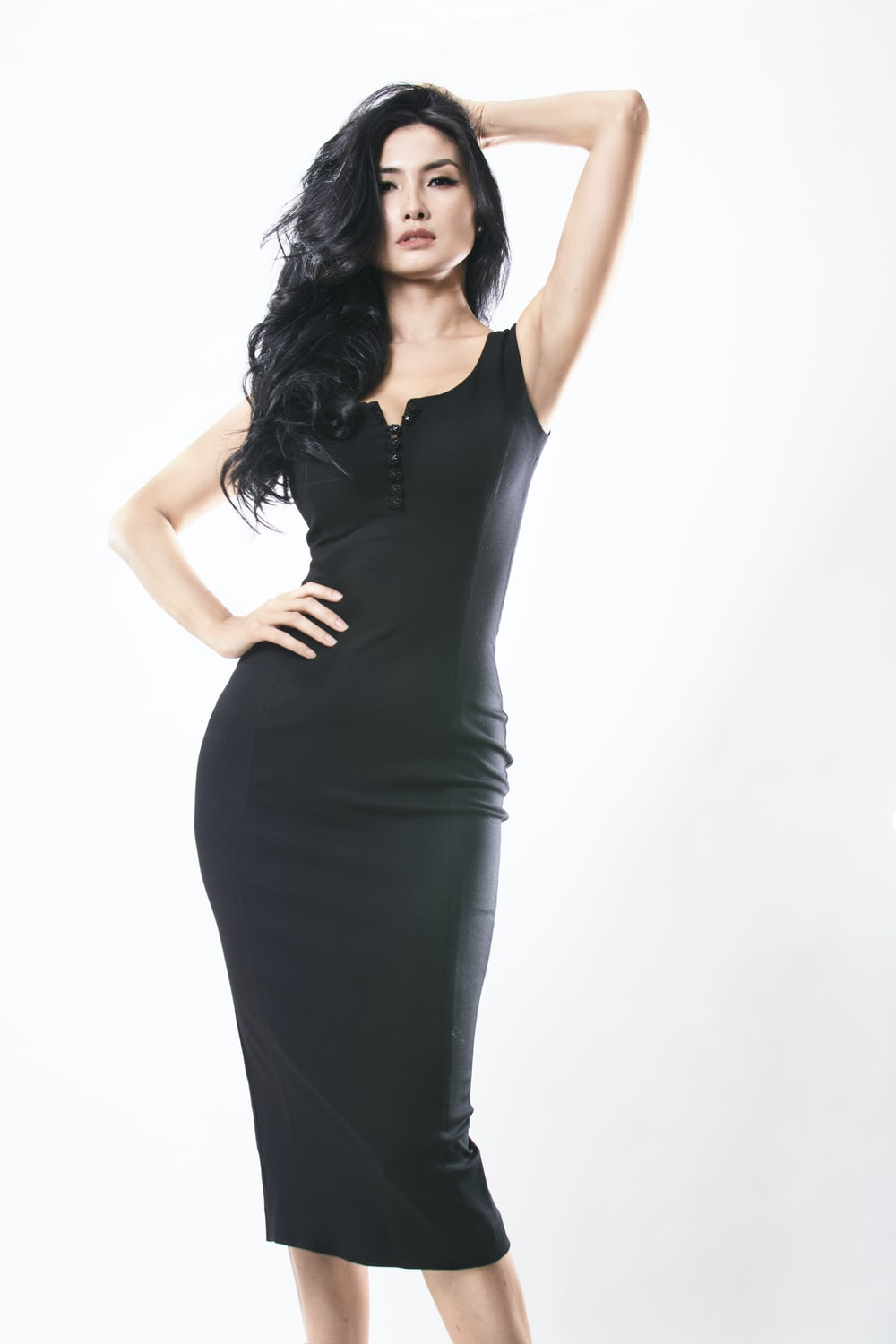 woman wearing black sleeveless dress holding hair with left hand