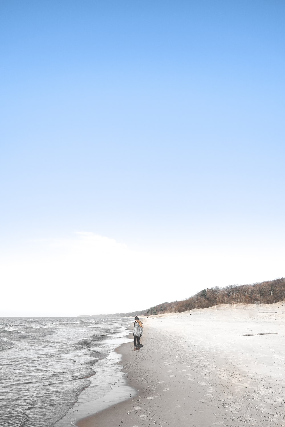 person standing on beach sand near sea water