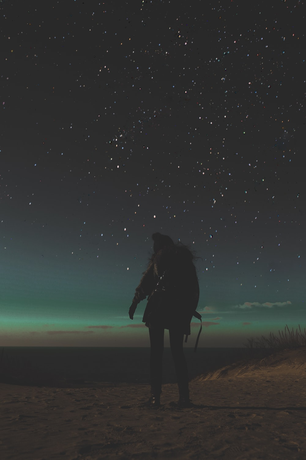 person standing on sand during nighttime