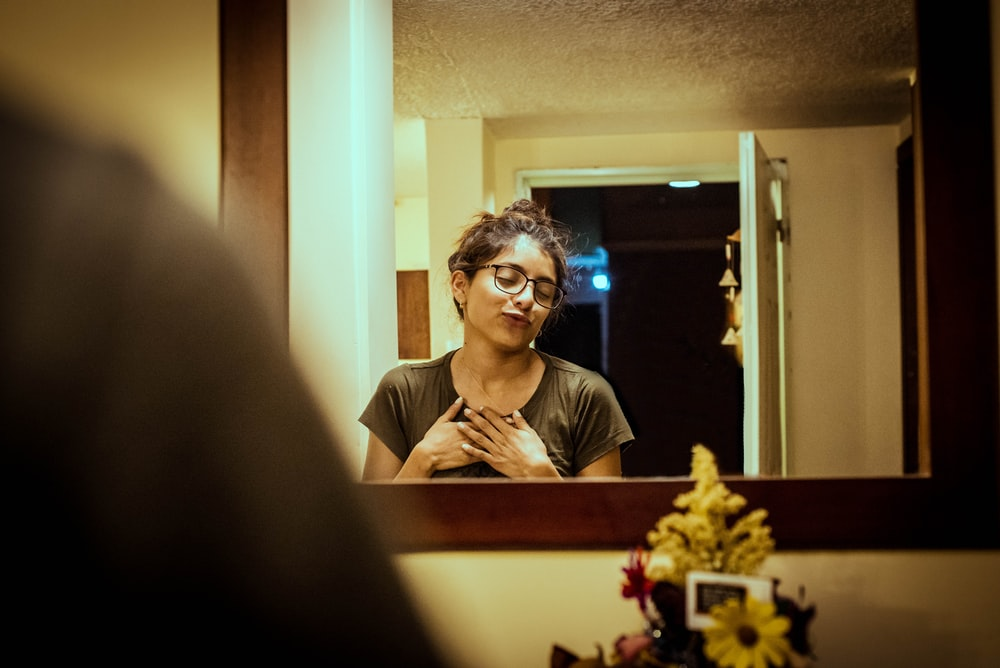 woman in gray shirt standing in front of wall mirror